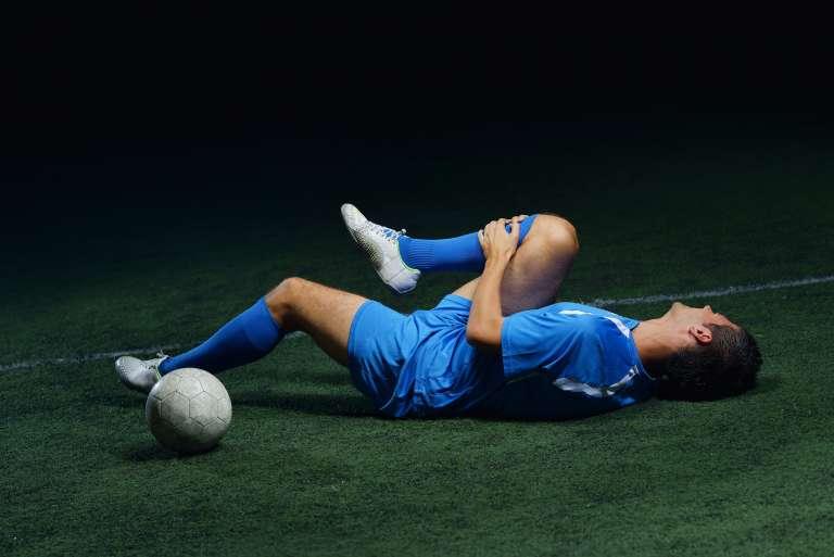 A photograph of a footballer, on the floor, holding their knee