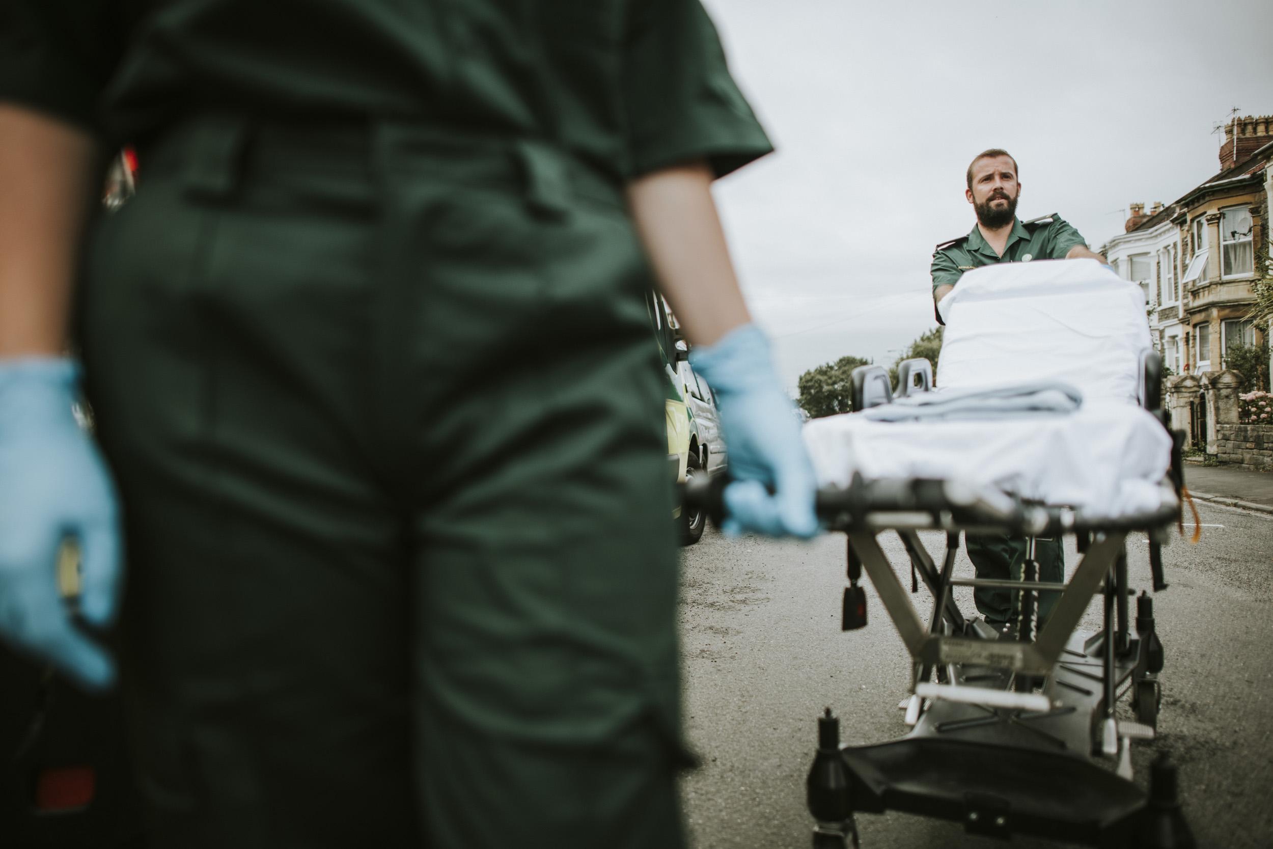 Paramedic team rolling a stretcher on a street