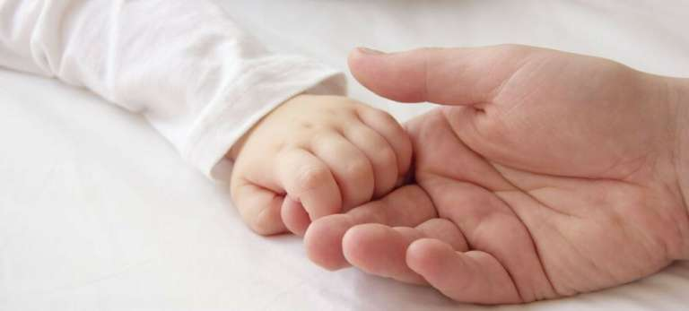 A photograph of a baby holding an adult's hand/finger. Pryers solicitors help people make birth injury claims.