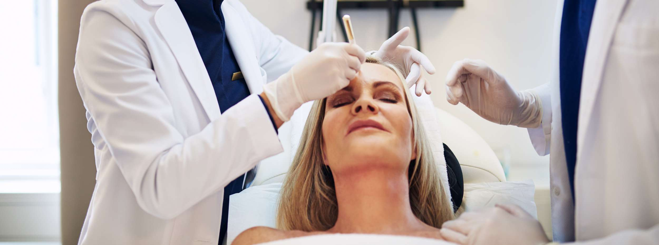 woman lying on clinic table before cosmetic surgery