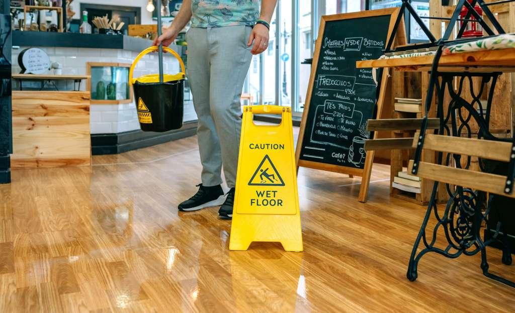 worker placing wet floor sign