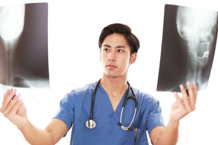 A photograph of a young doctor holding radiographs. This is the type of dcotr who might be involved in the doctors' strikes