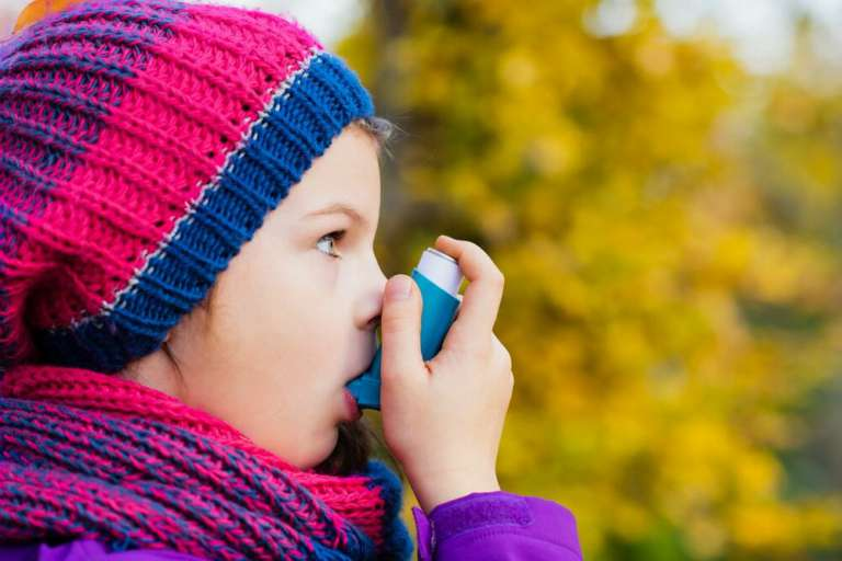 A photography of child using an inhaler. As research suggests that half a million children could have been wrongly diagnosed with asthma.