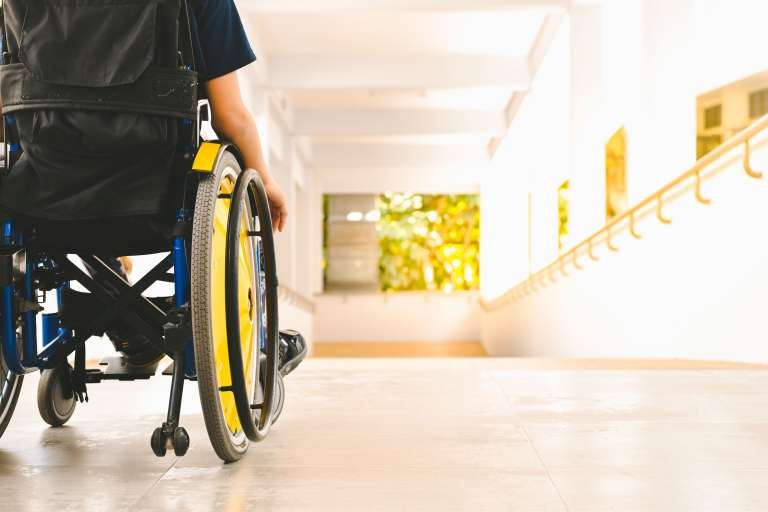 A photograph of a person in a wheelchair, taken from behind