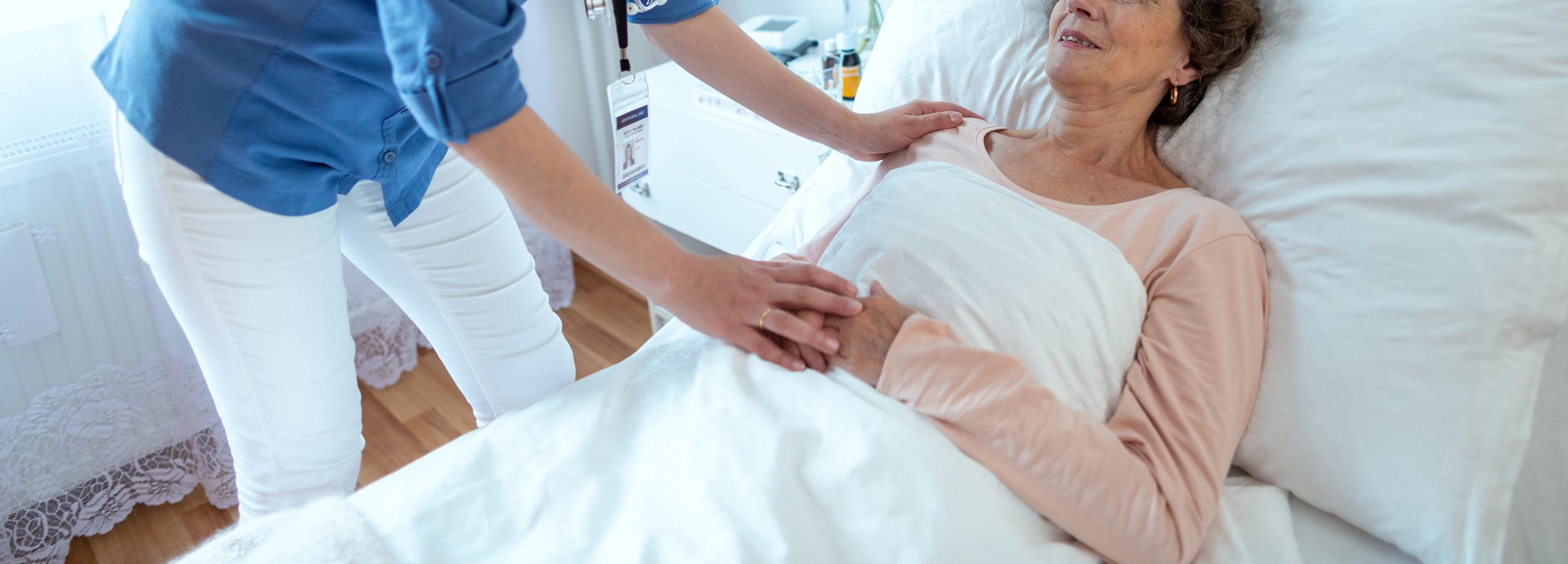 nurse leaning over elderly woman lying in hospital