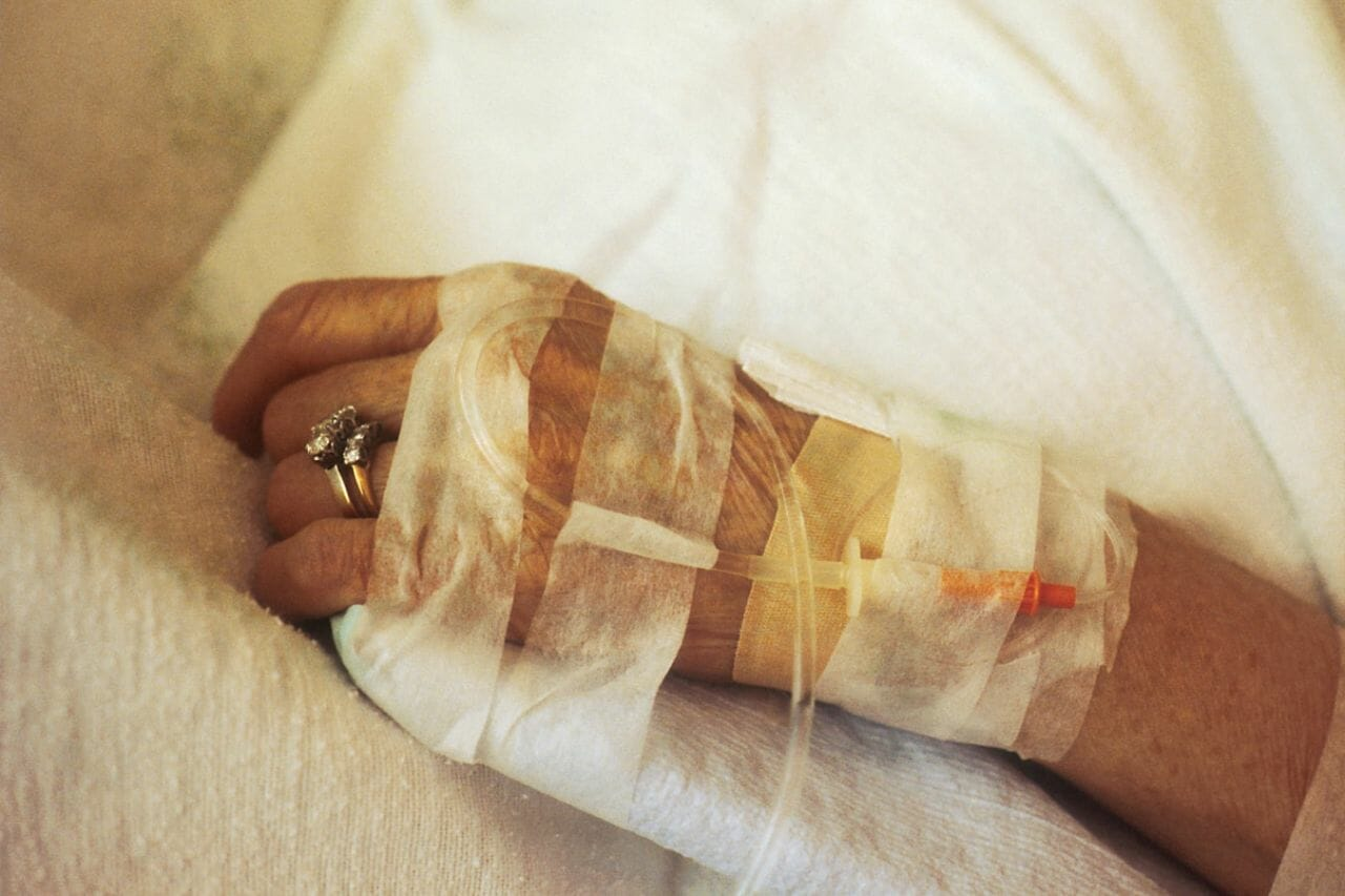 A close up photograph of hand receiving IV chemotherapy in an article about Waiting times for cancer treatments increasing.