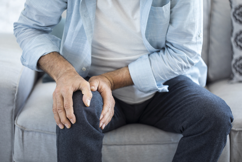 man with knee pain holding his knee