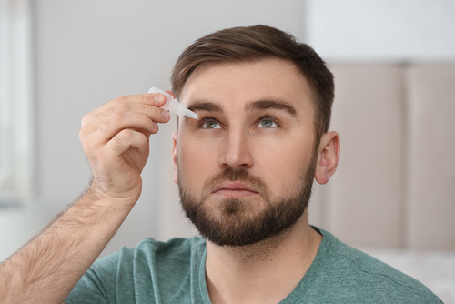 A photo of a man inserting eye drops into his eye