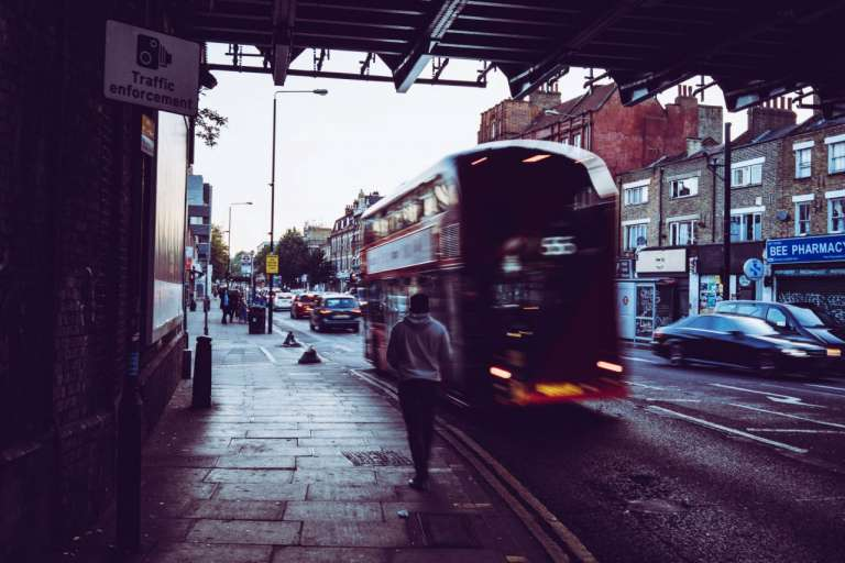 A photograph of an urban street. Featuring a pedestrian on a path and a bus on the road next to them. As a recent report highlighted concerns for vulnerable road users.