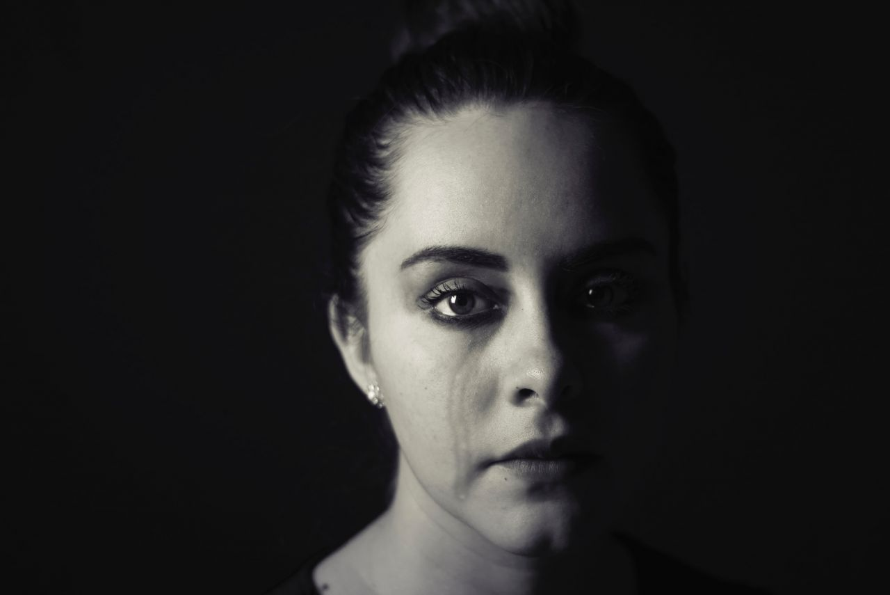 A lady crying against a black background
