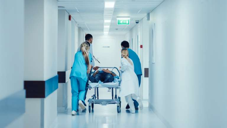 A photograph of a patient being wheeled through a hospital, on a bed, by medical staff.