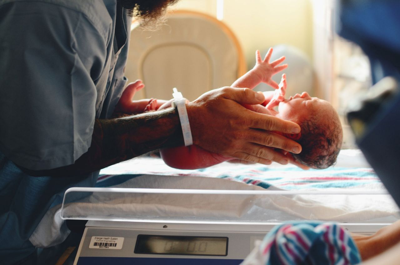 A photograph of a child after birth in hospital. NHS fees for migrants are putting babies, like this, and their mothers at risk.