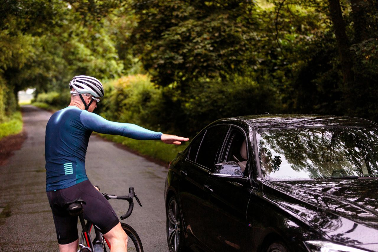 A cyclist converses with a driver.