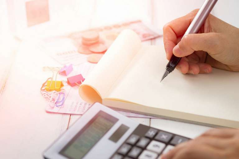 A photograph of a person writing on a notepad, with a calculator and money around them. They are calculating costs. This image is to depict the legal aid method of funding a medical negligence claim