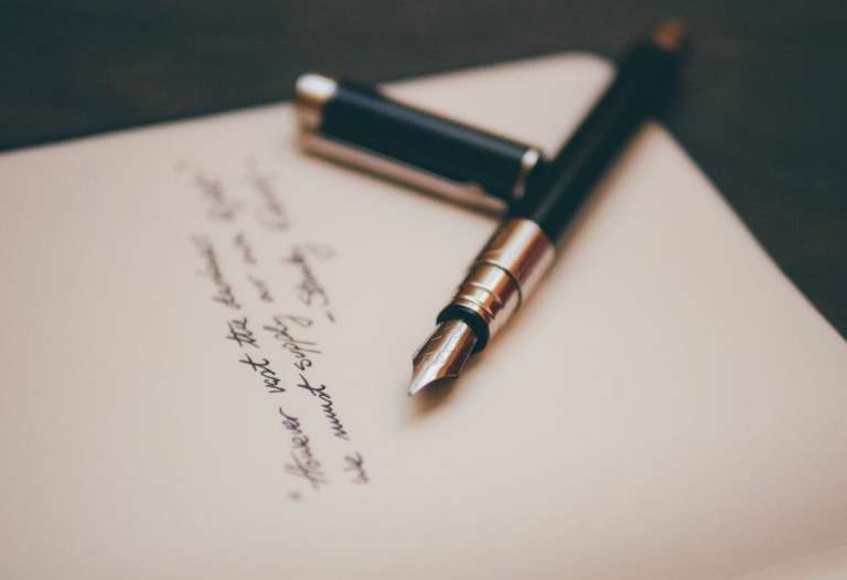 A photograph of a pen and paper with writing on it to depict the legal process you might have to go through, to claim compensation for the death of a loved one