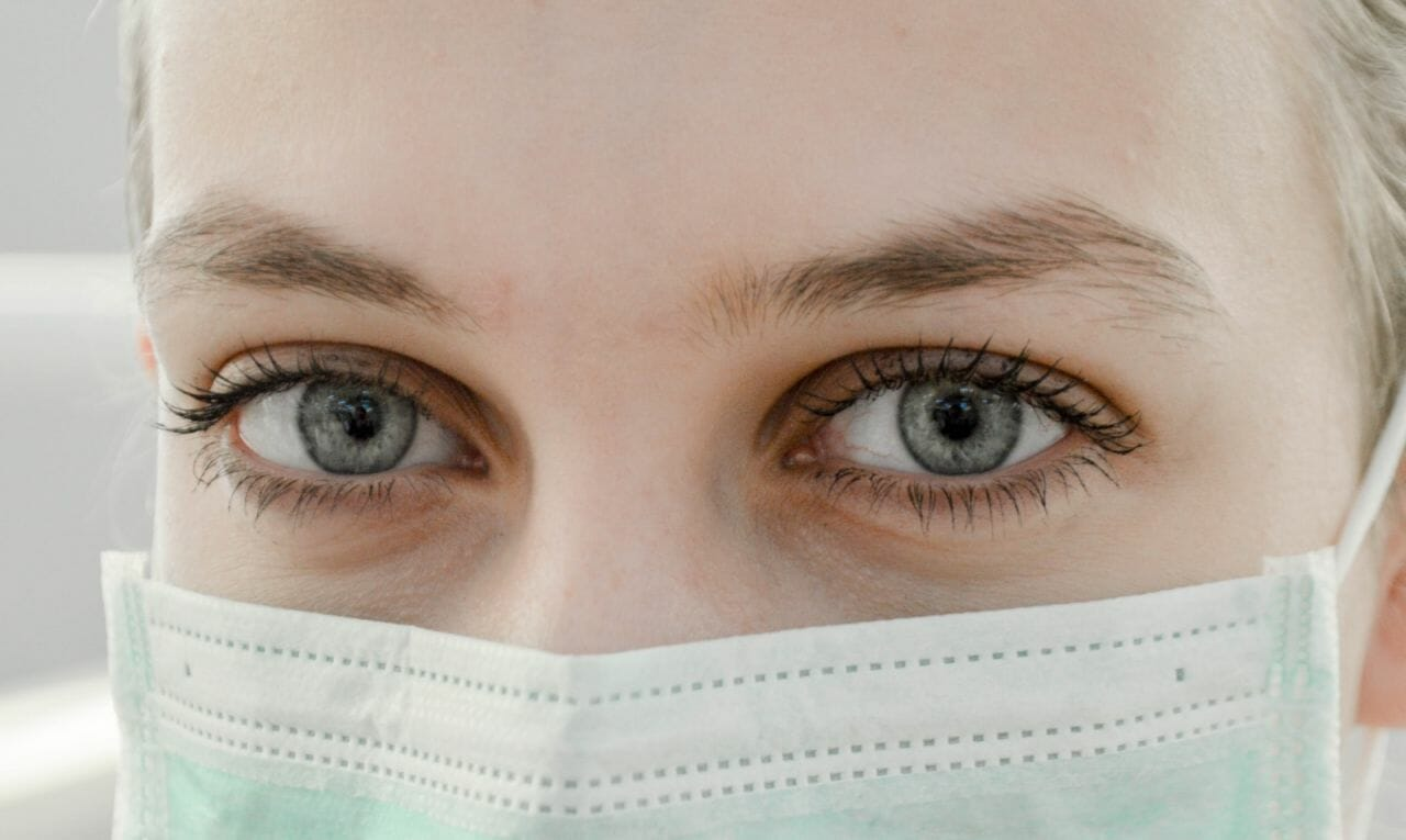 A nurse wearing a protective mask. These workers are some of those affected by NHS under-resourcing.