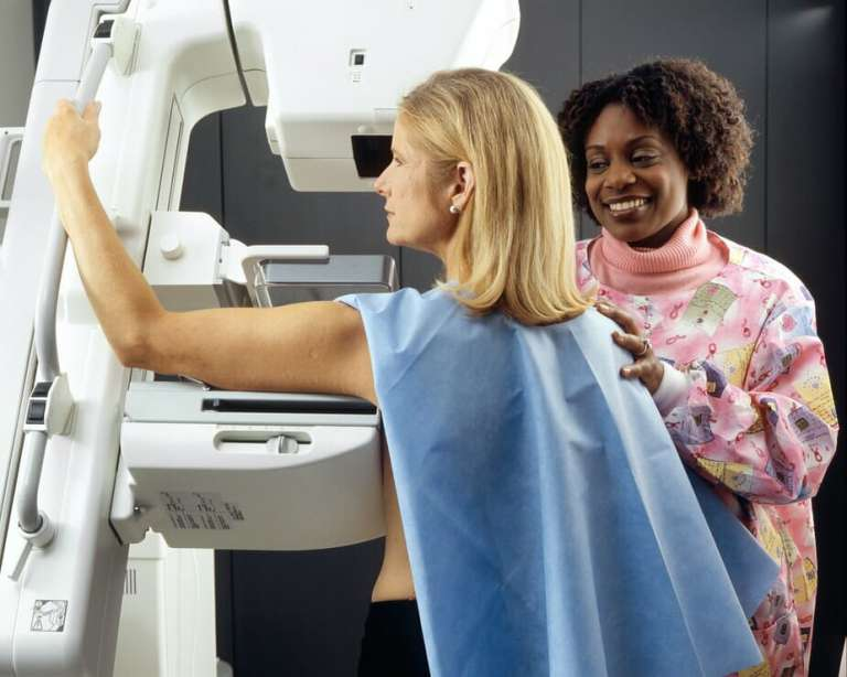 A photo of a lady having a mammogram. Part of vital cancer screening which is crucial to stop unnecessary cancer deaths