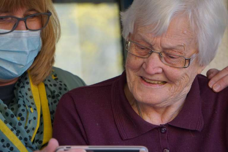 A photograph of an elderly lady, with somebody next to her holding a phone, as she smiles. The English government has been described as having a negligent approach to social care, in a damning report by the public accounts committee.