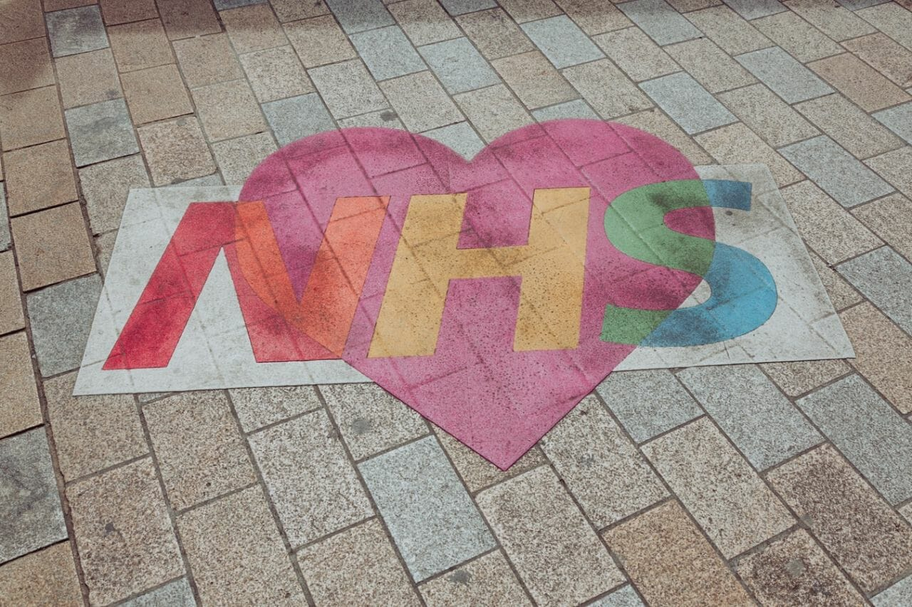 An image drawn on the pavement, in the UK, of the NHS logo with a heart - as a sign of appreciation, during the Coronavirus pandemic. Not long after, the Welsh government are accused of neglecting patients using the NHS.
