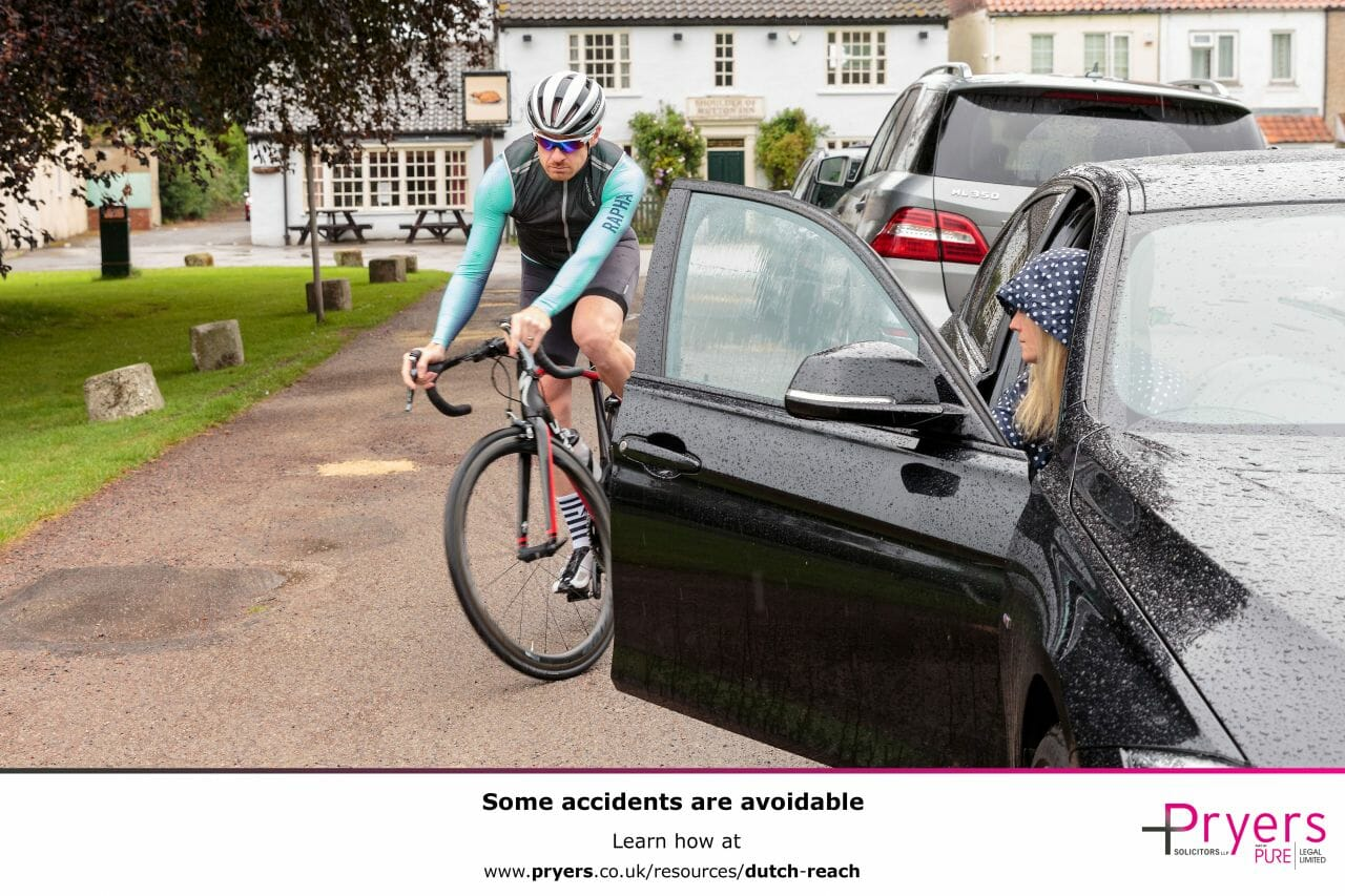 A poster showing a cyclist nearly getting knocked off, by the driver of a car, opening their door into the cyclist's path, with some text at the bottom encouraging people to learn the Dutch Reach.