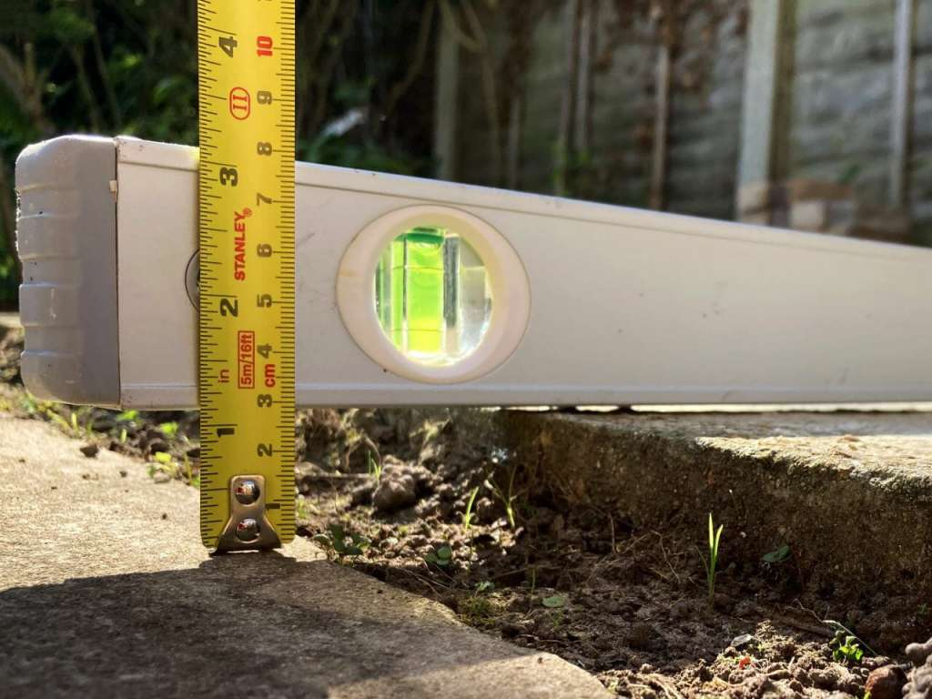 A photograph of a raised paving slab being measured. The same technique would be used when taking a photo of a pothole. It shows a straight edge over the top of the raised edge and a tape measure from the straight edge to the ground.
