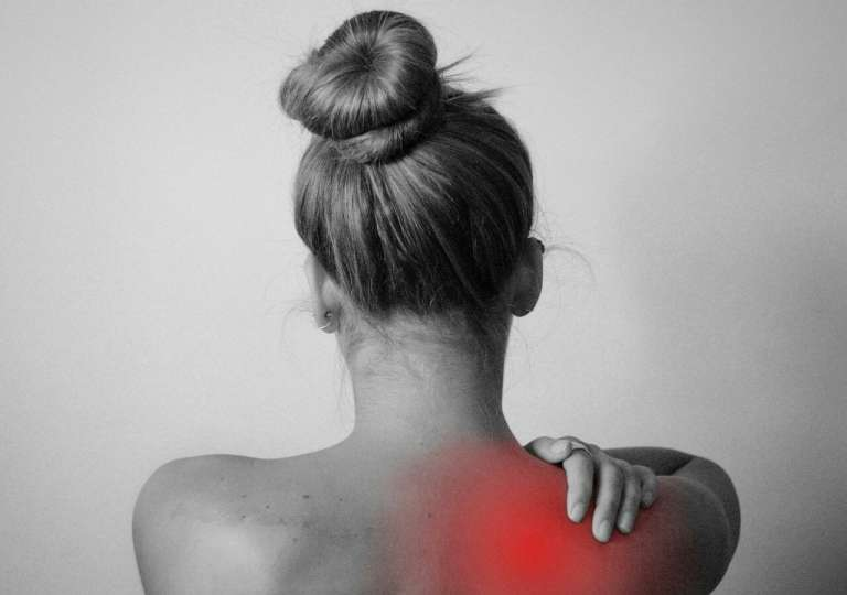 A photograph of a lady from behind, in black and white. The image has a red area added on her shoulder and she is grasping it, to depict pain, Mr Michael Walsh was an orthopaedic surgeon and operate on our client's shoulder