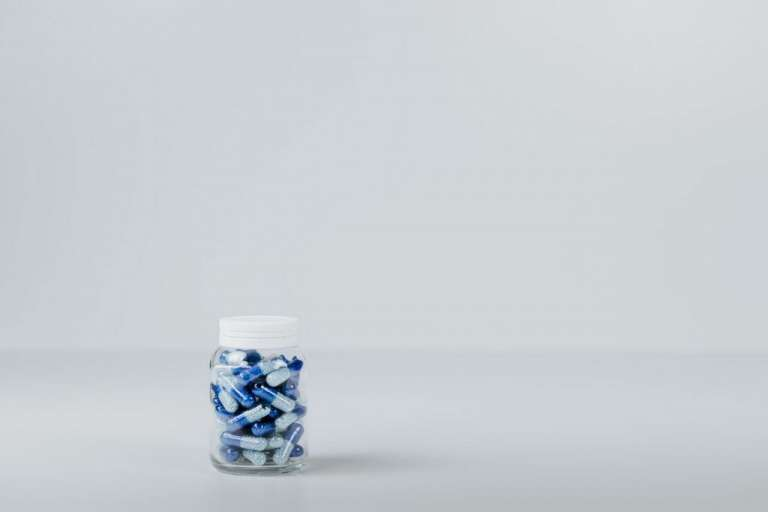 A photograph of blue medicine pills in a jar. The Cumberlege Review looked at issues arising from two medicines and a medical device.
