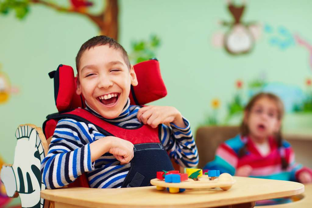 A photograph of a cheerful child, with cerebral palsy.