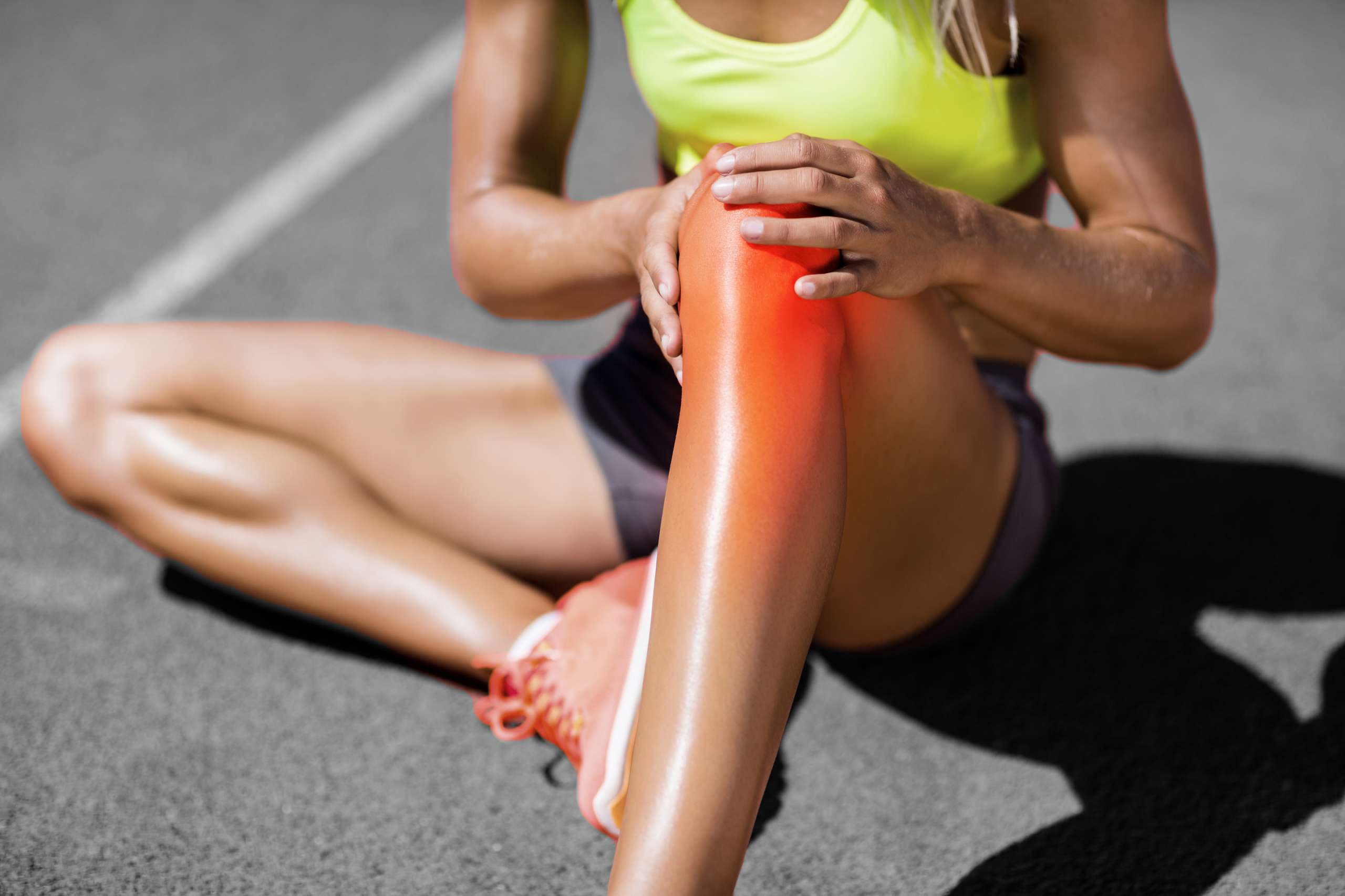 A photograph of a female athlete holding their knee, in pain,to depict the injury and problems following anterior cruciate ligament surgery that our client experienced