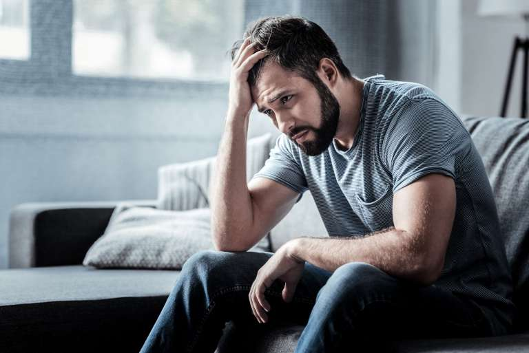 Man looking upset with head in hand