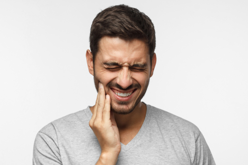Man in pain from toothache raising hand to face