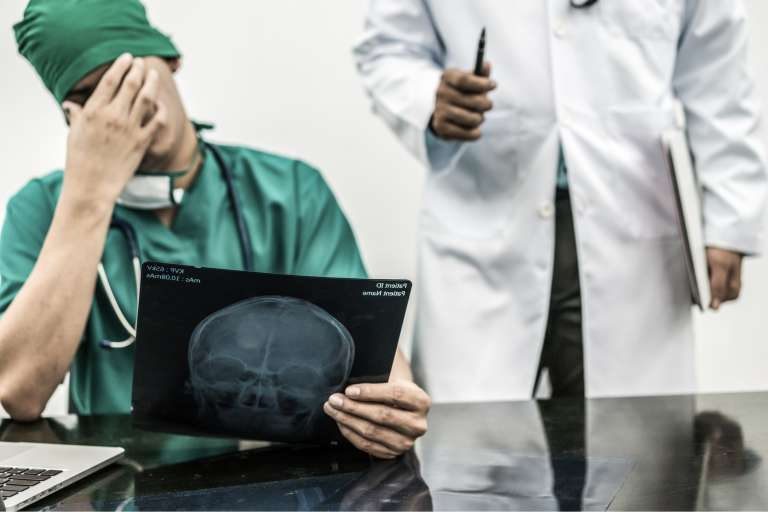 A photograph of a male doctor looking at a radiograph, with his head in his hand, to depict making a diagnostic error