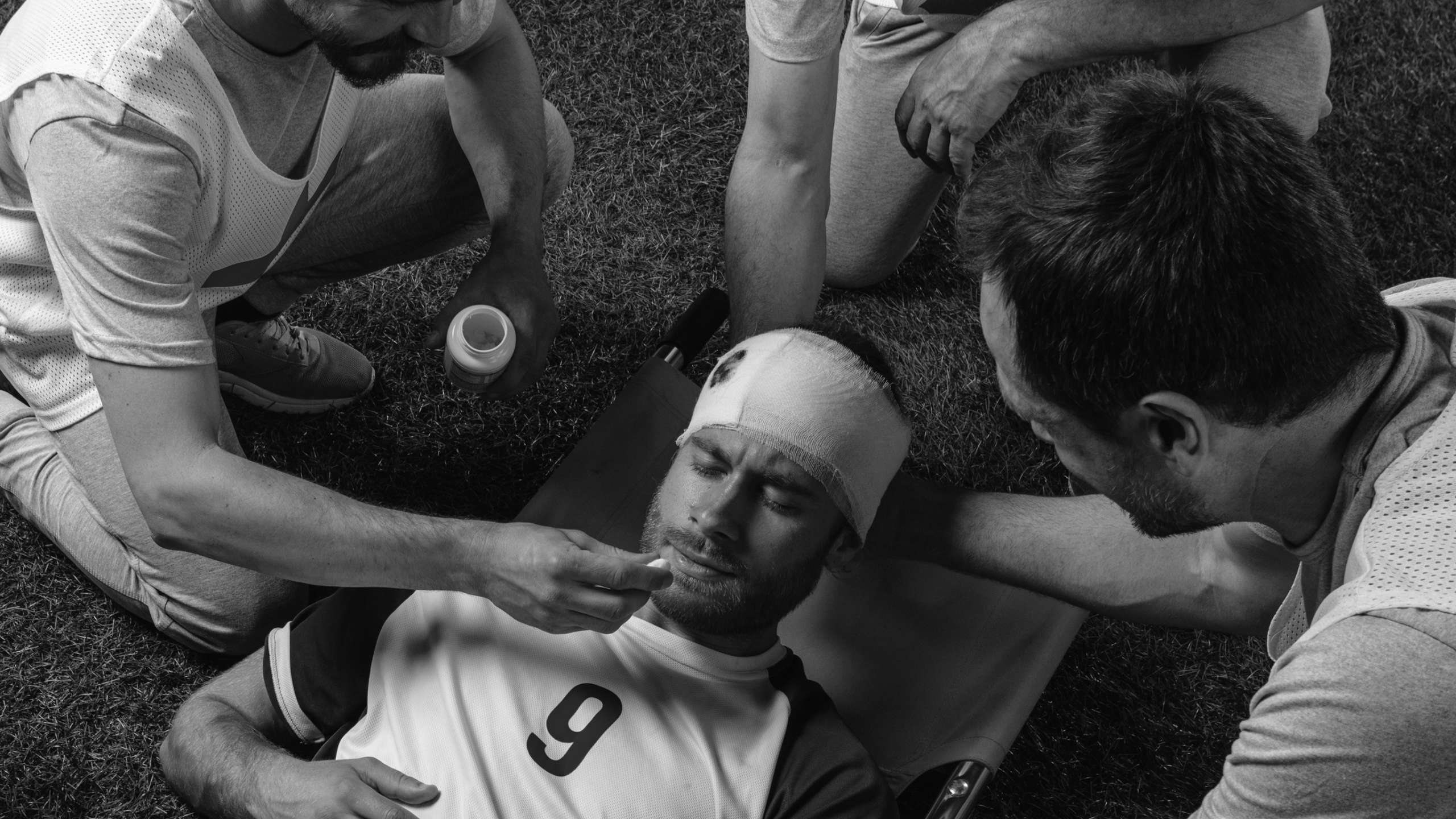 A black and white photo of a footballer with a head injury on a stretcher